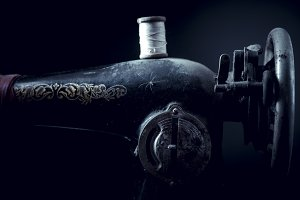 Old abandoned sewing machine on a black background