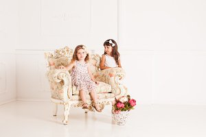 Two girls sits in a magnificent ancient armchair