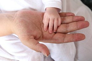 hands of a newborn girl and mother