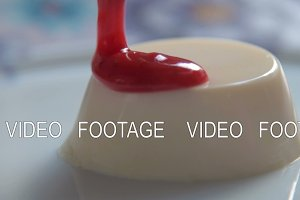 Pouring panna cotta with strawberry sauce