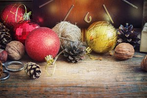 Christmas Composition red and yellow balls, cones,old clock in a basket on wooden background.Vintage style. toning