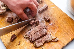 The cook cuts boiled beef meat