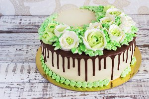 Celebratory cake with roses made of cream on a white wooden background