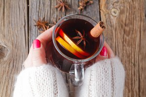 Hot mulled wine in female hands