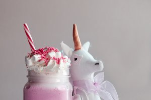 Toy unicorn with pink milk shake