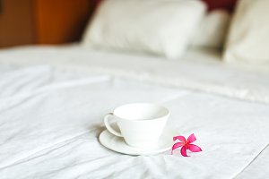 cup of tea and flower on the bed