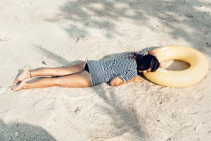girl lying on the beach, sunbathing and relaxing