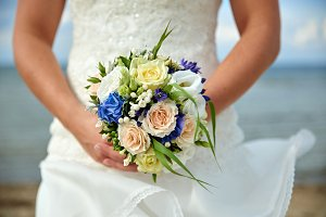bride holding wedding bouquet with roses