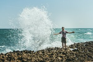 A young man stands on the shore in the spray from the crashing waves