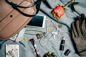 Stylish accessories from female handbag over grey background