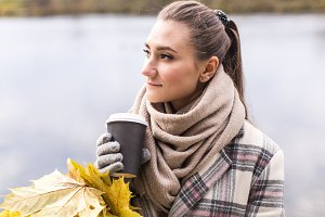 Girl drinking hot tea in park