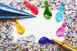 Background of confetti, hats and balloons. Copyspace. Carnival, party, celebration.