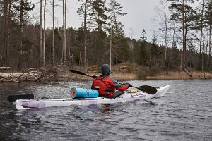 Free old kayaker paddle in norway lake after storm near forest island. Adventure concept. Outdoor sport and travel by water. Sea extreme tourism. Recreation time after live in big city.