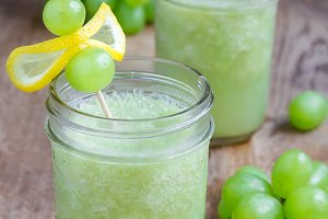 Healthy smoothie with green grape, lemon and honey in glass