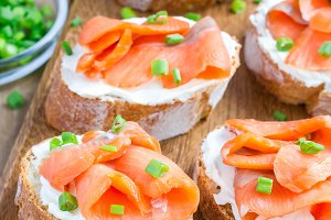Sandwich with smoked salmon and cream cheese, wooden board, vertical