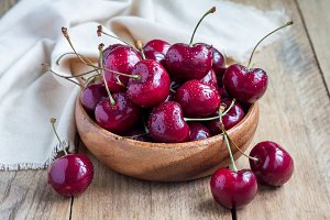 Cherries in wooden bowl with water drops, on table, horizontal