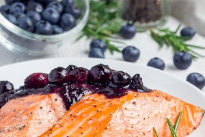 Baked salmon fillet with blueberry rosmarin sauce on white plate