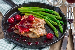 Pork cutlets with raspberry sauce and asparagus, horizontal
