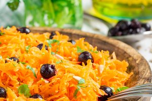 Healthy vegetarian salad with carrot, black currant, cilantro, sunflower, sesame