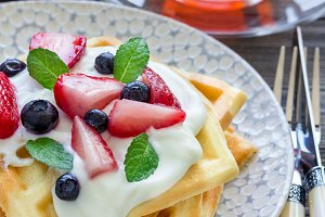 Homemade belgian waffles with yogurt, strawberry and blueberry, breakfast time