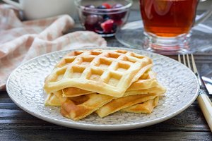 Homemade belgian waffles for breakfast, served with fruit and tea
