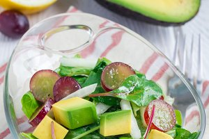 Vegetarian salad with avocado, grape, rucola, onion, in glass bowl