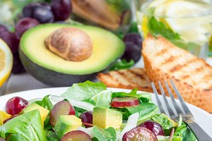 Vegetarian salad with avocado, grape, rucola, onion, vinegar dressing
