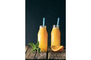 Two glass bottles of freshly squeezed orange juice with blue tubules on an old wooden table on a black background.