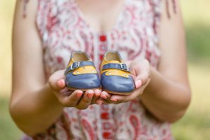 hand holds small baby shoes