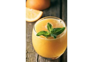 Top view on fresh orange juice in glass with mint leaf on a wooden rustic table.
