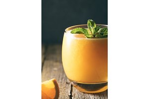 Close-up shot of fresh orange juice in glass with mint leaf on a wooden rustic table.