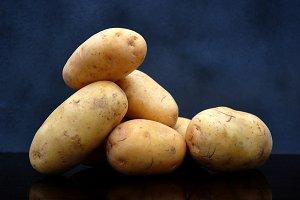Seven potatoes on dark