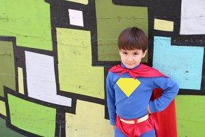 superhero kid in a graffiti wall