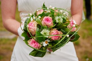 bride holding wedding bouquet pink roses