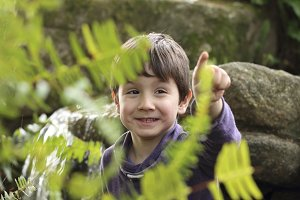 happy kid pointing a fern
