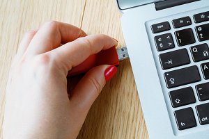 hand plugging a red pendrive