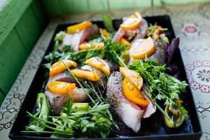 Homemade zander fish with vegetables and herbs