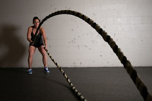Fitness Woman Working out with Ropes