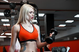 Portrait of a beautiful sexy woman dressed in sports clothes in the gym