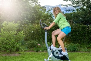 Beautiful blonde on theexercise  bike in the garden