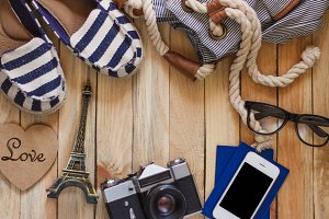 Striped slippers, camera, phone and miniature of Eiffel Tower, top view