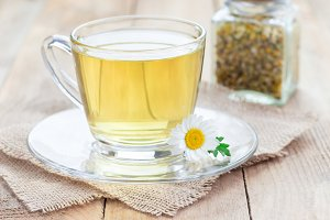Chamomile tea in glass cup, chamomile flowers and dry tea on background, horizontal