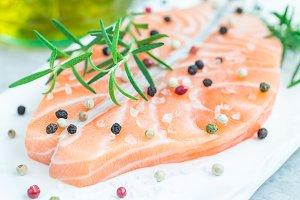 Fresh raw salmon steak with seasonings on white board, horizontal