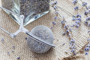 Dry lavender tea in tea infuser spoon and glass jag on wooden background, horizontal, closeup