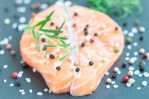 Fresh raw salmon steak with seasonings on stone board, horizontal, closeup