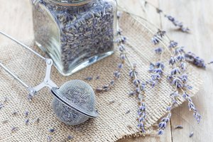 Dry lavender tea in tea infuser spoon and glass jag on wooden background, horizontal