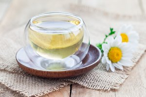 Chamomile tea in glass cup, chamomile flowers on background, horizontal