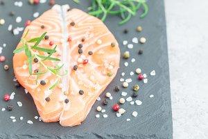Fresh raw salmon steak with seasonings on stone board, horizontal, copy space