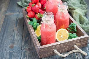 Homemade blended lemonade with fresh strawberry, lemon, ice and mint in glass bottle, horizontal, copy space