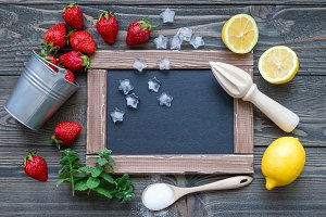 Ingredients for homemade strawberry lemonade on wooden table, around chalk board, top view, copy space